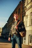Το όμορφο, βάναυσο άτομο στέκεται σε μια οδό πόλεων και εξετάζει τον ουρανό στοκ εικόνα με δικαίωμα ελεύθερης χρήσης