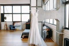 Το όμορφο γαμήλιο φόρεμα γυναικών ζυγίζει στις κρεμάστρες στη μεγάλη αίθουσα στον τοίχο στοκ εικόνα