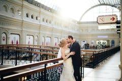 Το όμορφο γαμήλιο ζεύγος στη Μόσχα, η νύφη και ο νεόνυμφος σε ένα λευκό ντύνουν στην εσωτερική, ευτυχή νέα οικογένεια Στοκ Εικόνες