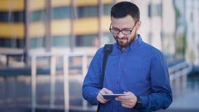 Το όμορφο γενειοφόρο άτομο με την τσάντα πέρα από τον ώμο του στο μπλε πουκάμισο και το καφετί παντελόνι στέκεται τα μηνύματα χρη απόθεμα βίντεο