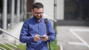 Το όμορφο γενειοφόρο άτομο που ντύνεται στο μπλε πουκάμισο και το καφετί παντελόνι στέκεται υπαίθρια και μηνύματα δακτυλογράφησης απόθεμα βίντεο