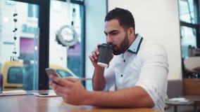 Το όμορφο γενειοφόρο άτομο σε ένα άσπρο επίσημο πουκάμισο χρησιμοποιεί το τηλέφωνό του για το Διαδίκτυο που κάνει σερφ πίνοντας τ απόθεμα βίντεο