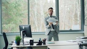 Το όμορφο γενειοφόρο άτομο στο κοστούμι χορεύει στο μόνο κινούμενο σώμα δωματίων γραφείων και οπλίζει έπειτα να πάρει τα έγγραφα  απόθεμα βίντεο