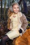 Το όμορφο γλυκό μικρό κορίτσι έντυσε σε ένα sheepskin παλτό και τις μπότες καθμένος στον κορμό και στο υπόβαθρο Στοκ φωτογραφία με δικαίωμα ελεύθερης χρήσης