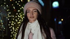 Το όμορφο ελκυστικό κορίτσι περπατά γύρω στο βράδυ δίπλα σε μια βιτρίνα που διακοσμείται με τα φω'τα και το κοίταγμα Χριστουγέννω απόθεμα βίντεο
