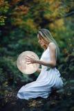 Το όμορφο ελκυστικό κορίτσι σε ένα άσπρο φόρεμα στο δάσος φθινοπώρου, αγκαλιάζει το φεγγάρι, ένα μυστήριο, μυστήριος ένας δασικός στοκ φωτογραφία με δικαίωμα ελεύθερης χρήσης