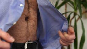 Το όμορφο επιχειρησιακό άτομο ξεκουμπώνει στενό επάνω πουκάμισών του απόθεμα βίντεο
