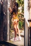 Το όμορφο λεπτό κορίτσι κίτρινο σε προκλητικό πλέκει το μαγιό σε μια πορεία στο α Στοκ Εικόνες