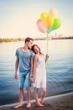 Το όμορφο ευτυχές ζεύγος με τη λαβή αγκαλιάσματος μπαλονιών παραδίδει την αγάπη outd Στοκ Εικόνα