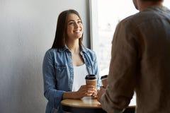 Το όμορφο ευτυχές κορίτσι με τη σκοτεινή τρίχα στην άσπρη μπλούζα κάτω από το πουκάμισο τζιν, πίνει τον καφέ και το χαμόγελο, ακο Στοκ Εικόνα
