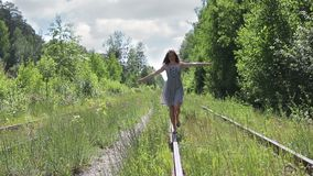 Το όμορφο ευτυχές κορίτσι πηγαίνει στην παλαιά ράγα μεταξύ του δάσους φιλμ μικρού μήκους