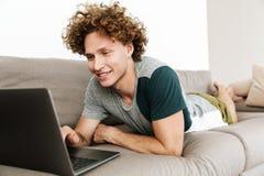 Το όμορφο εύθυμο άτομο βρίσκεται στον καναπέ χρησιμοποιώντας το φορητό προσωπικό υπολογιστή Στοκ εικόνα με δικαίωμα ελεύθερης χρήσης