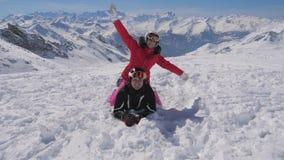 Το όμορφο ζευγάρι χιονοδρομικών κέντρων βουνών των σκιέρ που βρίσκεται στο χιόνι αυξάνει τα όπλα επάνω απόθεμα βίντεο