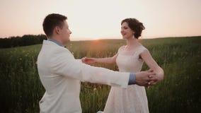 Το όμορφο ζεύγος ερωτευμένο εξετάζει το ένα το άλλο και το φιλί στη φύση στη ημέρα γάμου τους στο καλοκαίρι Θαυμάσιο ηλιοβασίλεμα απόθεμα βίντεο