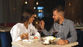 Το όμορφο ζεύγος ερωτευμένο κάθεται στον καφέ, καφές κατανάλωσης και κατανάλωση cheesecake Η νέα γυναίκα ταΐζει τον άνδρα της απόθεμα βίντεο