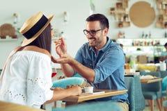 Το όμορφο ζεύγος ερωτευμένο κάθεται στον καφέ Ο νεαρός άνδρας ταΐζει τη γυναίκα και το χαμόγελό του στοκ εικόνα με δικαίωμα ελεύθερης χρήσης