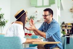 Το όμορφο ζεύγος ερωτευμένο κάθεται στον καφέ Ο νεαρός άνδρας ταΐζει τη γυναίκα και το χαμόγελό του στοκ φωτογραφία