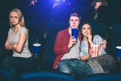 Το όμορφο ζεύγος κάθεται μαζί και κινηματογράφος προσοχής Το κορίτσι Brunette τρώει popcorn και ο τύπος πίνει το κοκ αυτή Στοκ εικόνα με δικαίωμα ελεύθερης χρήσης