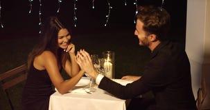 Το όμορφο ζεύγος κρατά τα χέρια πέρα από τον πίνακα γευμάτων απόθεμα βίντεο