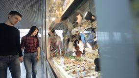 Το όμορφο ζεύγος των ανθρώπων θεωρεί τα αναμνηστικά στο κατάστημα στον αερολιμένα φιλμ μικρού μήκους