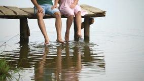 Το όμορφο ζεύγος youn κάθεται στην αποβάθρα κοντά στη λίμνη κάνετε τον παφλασμό από τα πόδια κίνηση αργή φιλμ μικρού μήκους