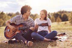 Το όμορφο θηλυκό εξετάζει με την αγάπη και την ευτυχία το φίλο της που παίζει την κιθάρα και τραγουδά τα ρομαντικά τραγούδια στον στοκ φωτογραφίες