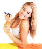 Το όμορφο θηλυκό εφαρμόζει τη suntan κρέμα Στοκ Φωτογραφία