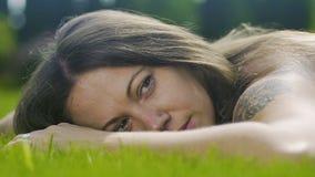 Το όμορφο θηλυκό με τη δερματοστιξία βρίσκεται στη χλόη που χαλαρώνουν κοιτάζει, προσέχοντας ξένοιαστο αργό απόθεμα βίντεο