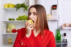 Το όμορφο θηλυκό πρότυπο το εύγευστο μήλο, σύνολο ψυγείων στάσεων πλησίον ανοιγμένο των υγιών προϊόντων, demonstares το καλό nutr στοκ φωτογραφία με δικαίωμα ελεύθερης χρήσης