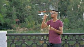 Το όμορφο ινδικό αγόρι στις επιστολές γυαλιών σαπουνίζει τις φυσαλίδες στην ακτή ποταμών απόθεμα βίντεο