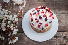 Το όμορφο κέικ Πάσχας στέκεται σε μια ξύλινη επιφάνεια, στο υπόβαθρο το ανθίζοντας βερίκοκο Στοκ Εικόνες