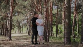 Το όμορφο και ευτυχές αγαπώντας ζεύγος αγκαλιάζει tenderly στο δάσος απόθεμα βίντεο