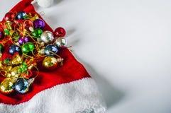 Το όμορφο καπέλο Χριστουγέννων, παρουσιάζει και Χριστουγέννων σφαίρες σε μια κόκκινη ΚΑΠ Στοκ φωτογραφίες με δικαίωμα ελεύθερης χρήσης