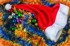 Το όμορφο καπέλο Χριστουγέννων, παρουσιάζει και Χριστουγέννων σφαίρες σε μια κόκκινη ΚΑΠ Στοκ Εικόνα