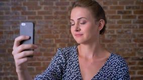Το όμορφο καυκάσιο κορίτσι brunette έχει την τηλεοπτική κλήση και κυματίζει στο smartphone της με το χαμόγελο και τη χαρά κοντά σ φιλμ μικρού μήκους