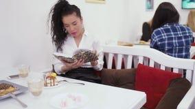 Το όμορφο καυκάσιο brunette διάβασε το βιβλίο και απολαμβάνει τη μοναξιά στον καφέ απόθεμα βίντεο