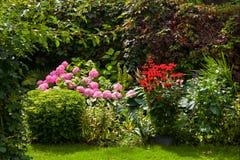 Το όμορφο καλοκαίρι σχεδίασε τον ανθίζοντας επίσημο κήπο Στοκ Εικόνες