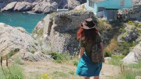 Το όμορφο κοκκινομάλλες κορίτσι σε ένα καπέλο κάουμποϋ περπατά μέσω των βουνών θαλασσίως φιλμ μικρού μήκους