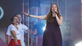 Το όμορφο κοκκινομάλλες κορίτσι τραγουδά και χορεύει Τραγουδιστής στη συναυλία Στο φεστιβάλ χορεύοντας κορίτσι δίσκων με την μικρ φιλμ μικρού μήκους