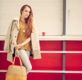 Το όμορφο κοκκινομάλλες κορίτσι με μια μοντέρνη τσάντα στο χέρι αξίζει κοντά στον κλειστό υπαίθριο καφέ Στοκ Εικόνες