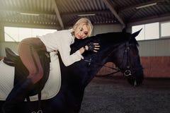 Το όμορφο κομψό νέο ξανθό κορίτσι βρίσκεται σε ένα μαύρο άλογό της ντύνοντας το ομοιόμορφο πουκάμισο μπλουζών ανταγωνισμού άσπρο  στοκ φωτογραφία
