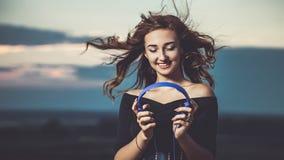 Το όμορφο κορίτσι έβαλε στα ακουστικά σε επικεφαλής και το άκουσμα στη μουσική στη φύση στον τομέα στοκ εικόνα