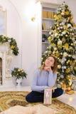 Το όμορφο κορίτσι έλαβε το δώρο στην παραμονή των Χριστουγέννων και θέτει και s Στοκ εικόνες με δικαίωμα ελεύθερης χρήσης