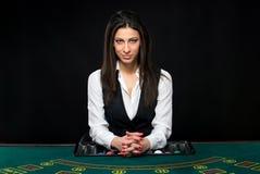 Το όμορφο κορίτσι, έμπορος, πίσω από έναν πίνακα για το πόκερ Στοκ Εικόνες
