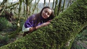 Το όμορφο κορίτσι έρχεται στο δέντρο και αγγίζει το βρύο και θέλει να πέσει κοιμισμένη σε το απόθεμα βίντεο