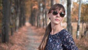 Το όμορφο κορίτσι αγγίζει την τρίχα της και χαμογελά στο δάσος φθινοπώρου απόθεμα βίντεο
