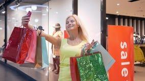 Το όμορφο κορίτσι αγοραστών φωτογραφίζεται στο κινητό τηλέφωνο με τις φωτεινές τσάντες αγορών κατά τη διάρκεια των αγορών στα κατ απόθεμα βίντεο