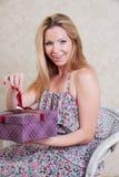 Το όμορφο κορίτσι ανοίγει ένα δώρο Στοκ Φωτογραφίες
