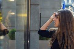 Το όμορφο κορίτσι αυξάνει τα γυαλιά ηλίου της και εξετάζει την προθήκη ο Στοκ φωτογραφία με δικαίωμα ελεύθερης χρήσης