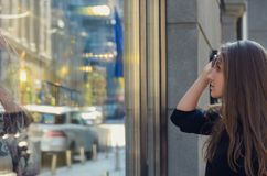 Το όμορφο κορίτσι αυξάνει τα γυαλιά ηλίου της και εξετάζει την προθήκη ο Στοκ εικόνα με δικαίωμα ελεύθερης χρήσης